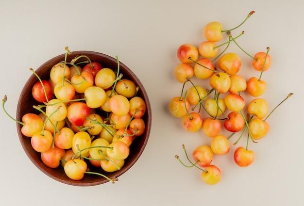 Vista superior del tazón de cerezas amarillas con cerezas en superficie blanca