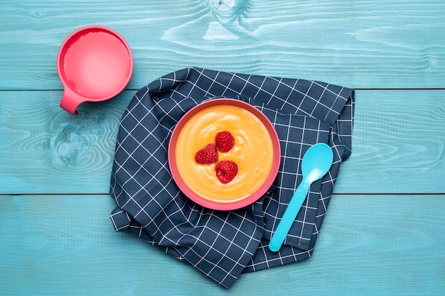 Vista superior del tazón con comida para bebés y fruta.