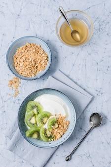 Vista superior del tazón de desayuno con yogur y kiwi