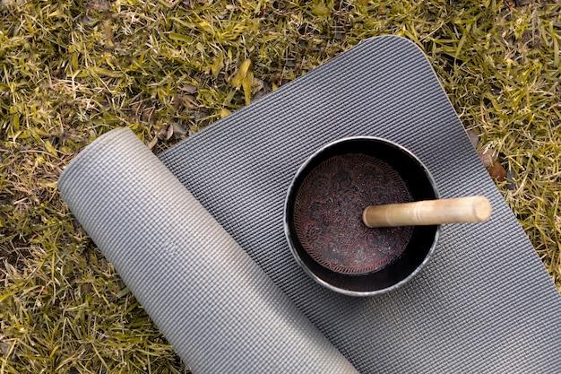 Vista superior del tazón de firma con estera de yoga en la hierba