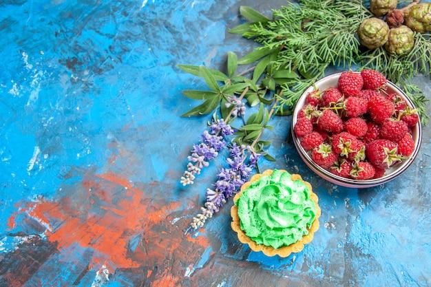 Vista superior del tazón de frambuesa y tarta pequeña sobre superficie azul