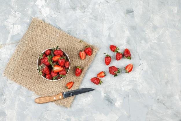 Vista superior de un tazón de fresas en un pedazo de saco con un cuchillo sobre la superficie de mármol blanco.