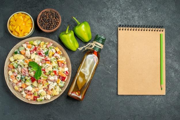 Vista superior del tazón de fuente de ensalada de verduras con tazones de fuente de pimiento y verduras botella de aceite pimientos y bloc de notas en el lado de la mesa oscura