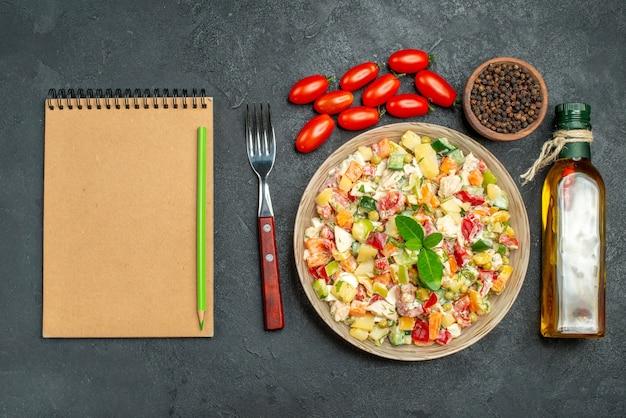 Vista superior del tazón de fuente de ensalada de verduras con tenedor, botella de aceite, tomates, pimienta y bloc de notas en el lado sobre fondo gris oscuro