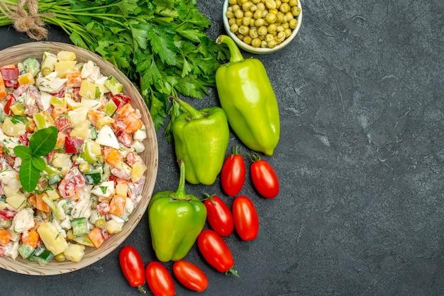 Vista superior del tazón de fuente de ensalada de verduras con verduras a un lado con espacio libre para el texto sobre fondo gris oscuro