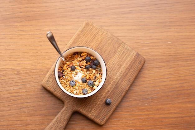 Vista superior tazón de granola casero con yogur griego y arándanos sobre fondo marrón, desayuno o merienda saludable