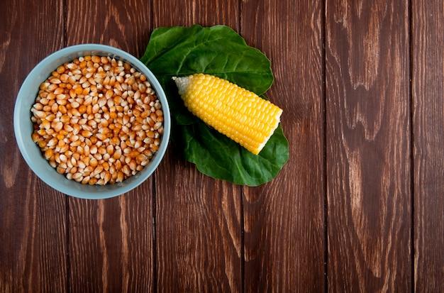 Vista superior del tazón lleno de granos de maíz seco con maíz cocido cortado y espinacas en la superficie de madera con espacio de copia