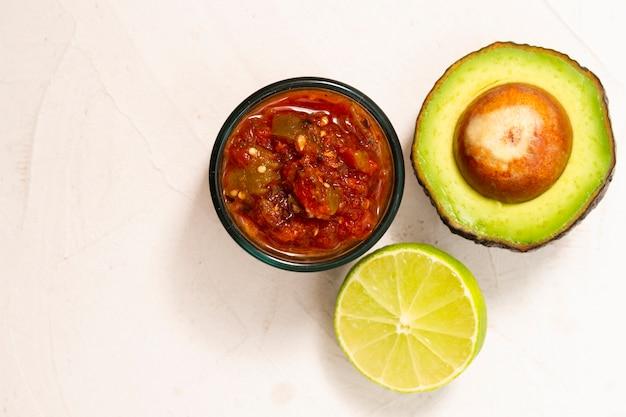 Vista superior tazón de salsa cerca de aguacate y lima