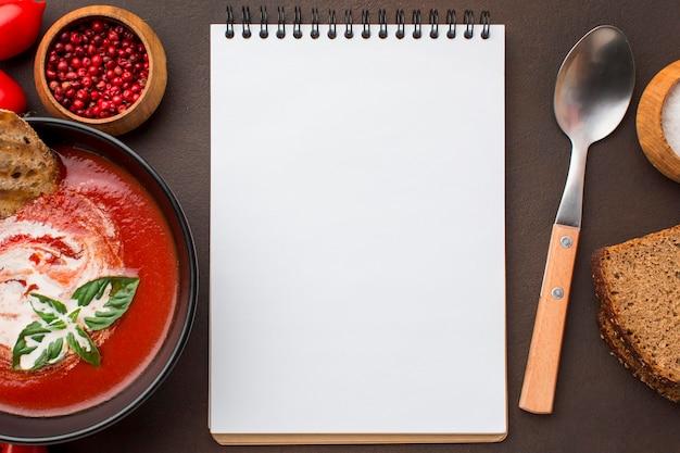 Vista superior del tazón con sopa de tomate de invierno y portátil