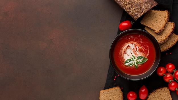 Vista superior del tazón con sopa de tomate de invierno en tazón y tostadas