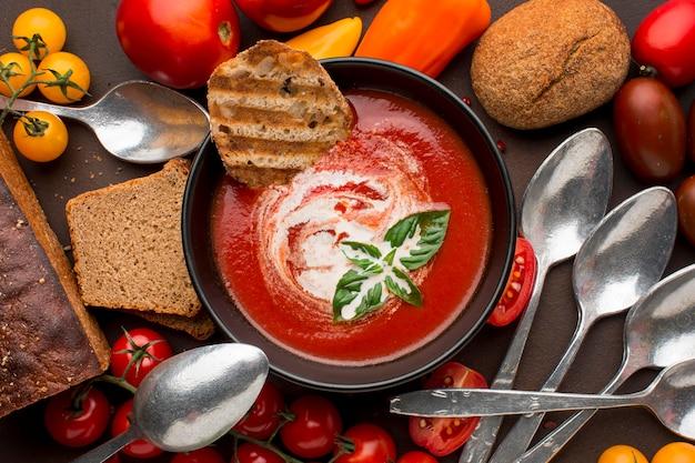 Vista superior del tazón con sopa de tomate de invierno y tostadas