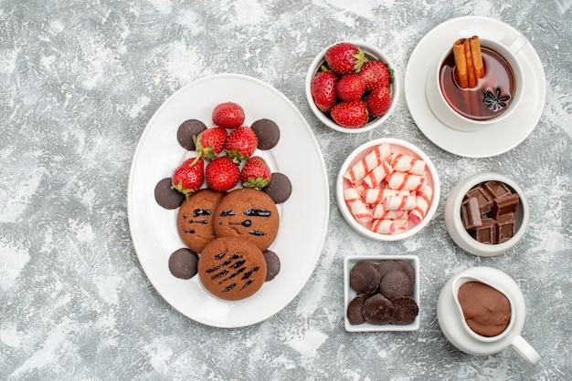 Vista superior tazones de galletas, fresas y chocolates con caramelos de cacao, fresas, chocolates y té con canela en el lado derecho de la mesa gris-blanca