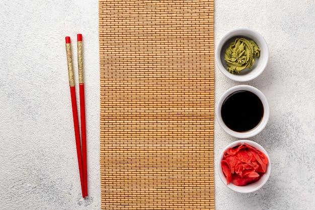 Vista superior tazones de salsa de soja y wasabi de jengibre con tapa de mesa