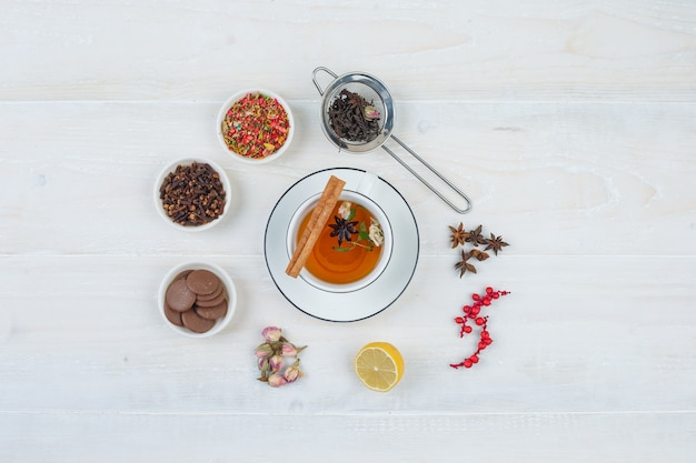 Vista superior de té de hierbas y galletas con colador de té, hierbas y especias sobre superficie blanca