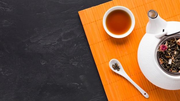 Vista superior de té de hierbas en mantel naranja