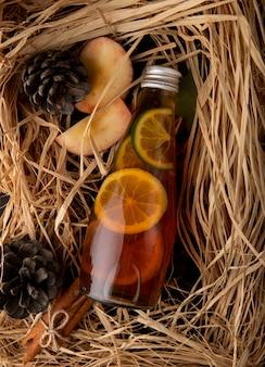 Vista superior de té de limón con canela en rodajas de manzana roja y cono de abeto en la paja