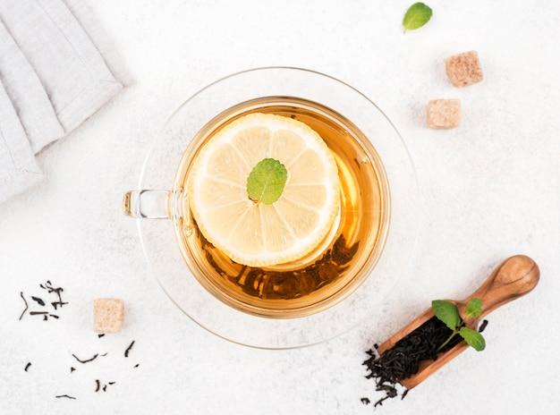 Vista superior de té con limón en el escritorio