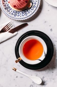 Vista superior del té de manzana en vidrio de porcelana con plato y cuchara servido con rosa y lichis mousses