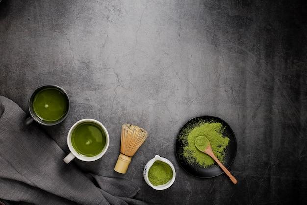 Vista superior del té matcha en tazas con batidor de bambú y espacio de copia