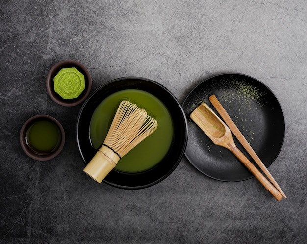 Vista superior del té matcha en un tazón con batidor de bambú y cuchara de madera