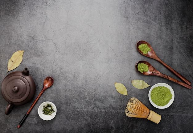 Vista superior de té matcha con tetera y cucharas de madera