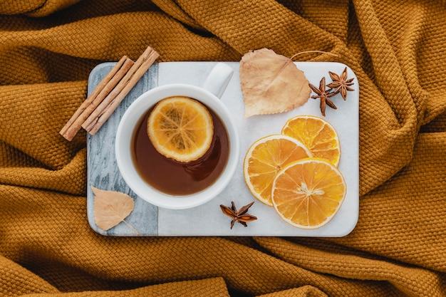 Vista superior de té con rodajas de limón secas y canela en rama a bordo