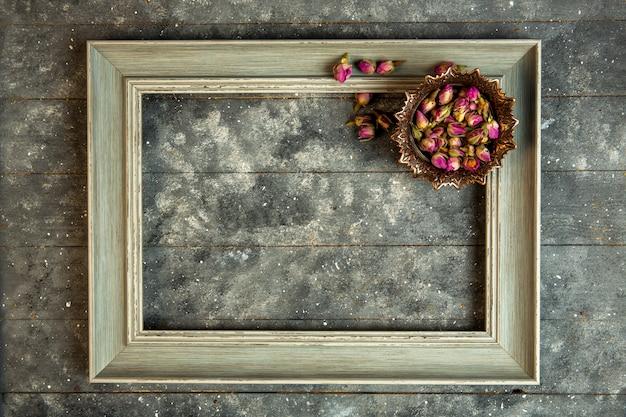 Vista superior de té de rosas en un tazón y un marco vacío de madera