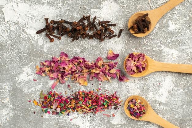 Vista superior de té seco coloreado sobre la superficie blanca polvo de sabor de árbol de planta de flor