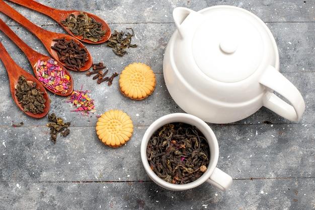 Vista superior de té seco fresco con galletas y hervidor de agua en el escritorio rústico gris