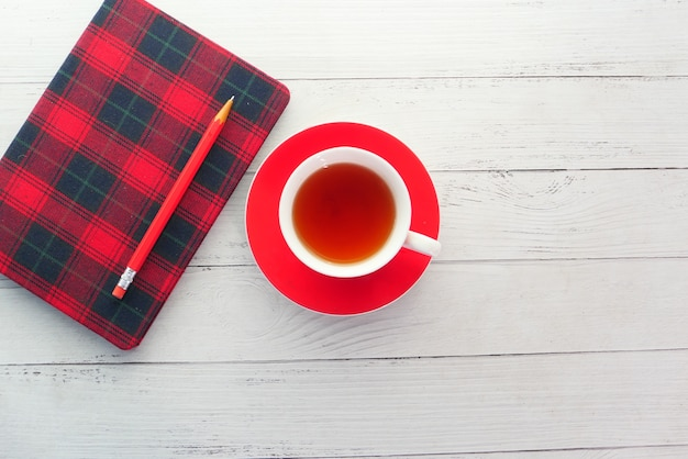 Vista superior del té verde y el bloc de notas en la mesa de madera