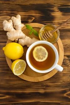 Vista superior de té verde con limón, miel y jengibre en la tabla de cortar de madera