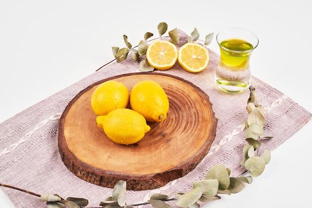 Vista superior de té verde con limones sobre mantel marrón.