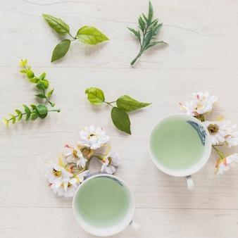 Vista superior de té verde en tazas con hojas y flores frescas