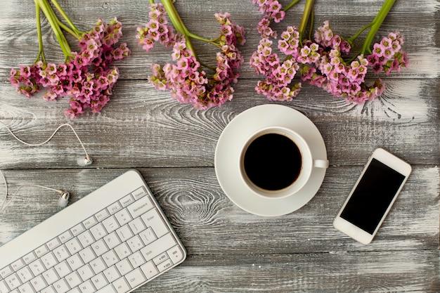 Vista superior de un teclado, auriculares y una taza de café, teléfono y una flor morada en una mesa de madera gris. diseño plano.