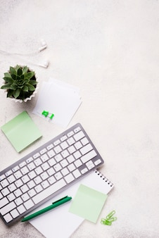Vista superior del teclado en el escritorio con plantas suculentas y notas adhesivas