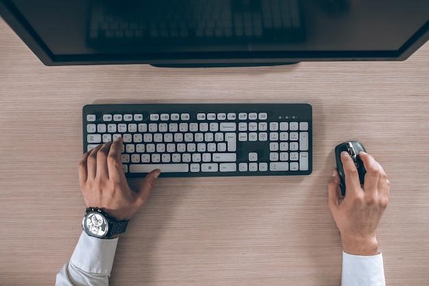 Vista superior del teclado con las manos de los hombres. espacio libre de copia del monitor negro para el diseño