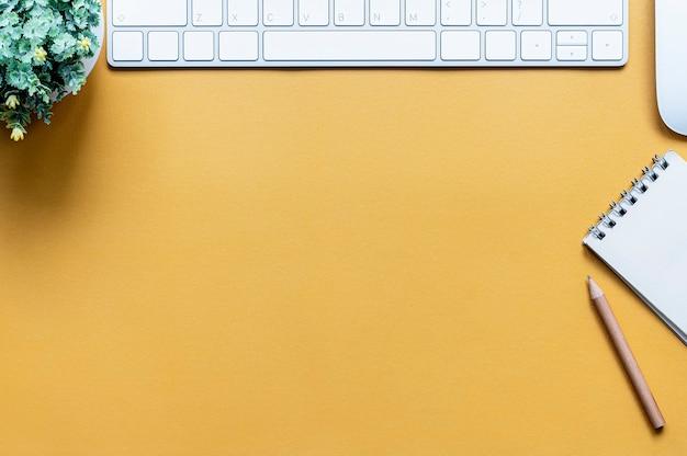 Vista superior del teclado, mouse, bloc de notas y lápiz de computadora sobre la mesa.