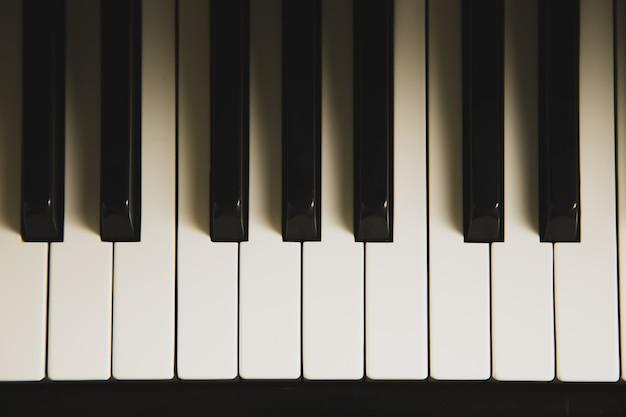 Vista superior del teclado del piano con iluminación y sombra.