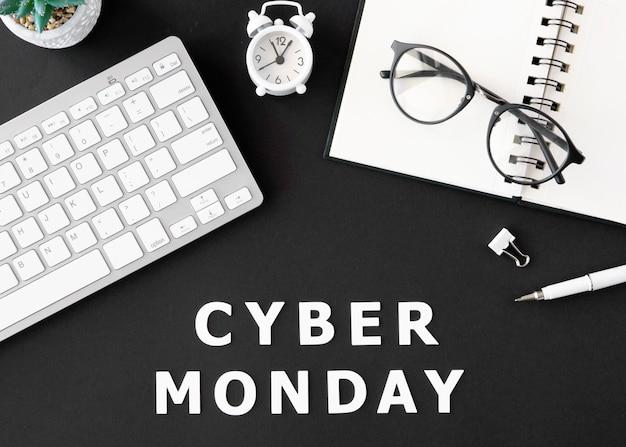 Vista superior del teclado con portátil y gafas para cyber monday