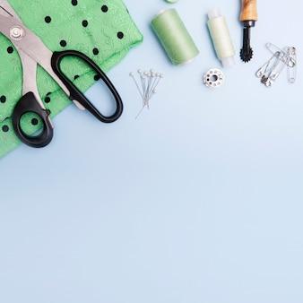 Vista superior de la tela, hilos y suministros de costura sobre un fondo azul. el concepto de coser ropa. copia espacio
