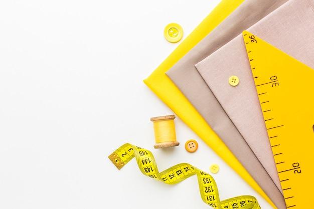 Vista superior de telas con hilo y cinta métrica