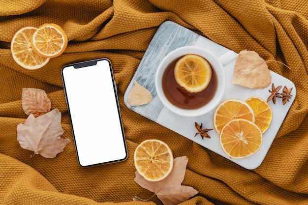 Vista superior del teléfono en blanco con té y rodajas de limón secas