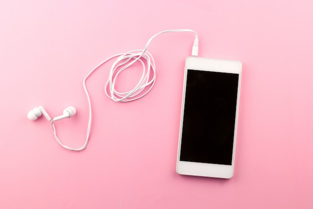 Vista superior del teléfono celular con fondo rosa auriculares