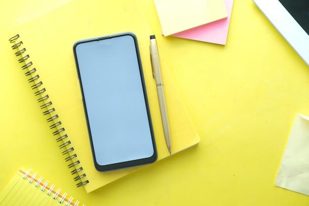 Vista superior del teléfono inteligente y el bloc de notas en amarillo