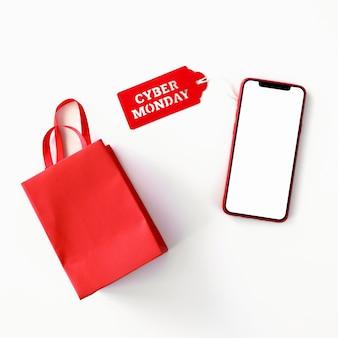 Vista superior del teléfono inteligente con bolsa de compras y etiqueta de cyber monday