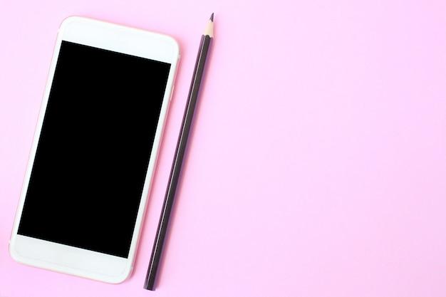 Vista superior del teléfono inteligente y el crayón en el piso rosa y tiene espacio para copiar.