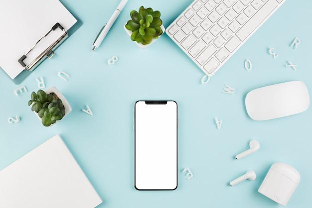 Vista superior del teléfono inteligente en el escritorio con teclado y suculentas