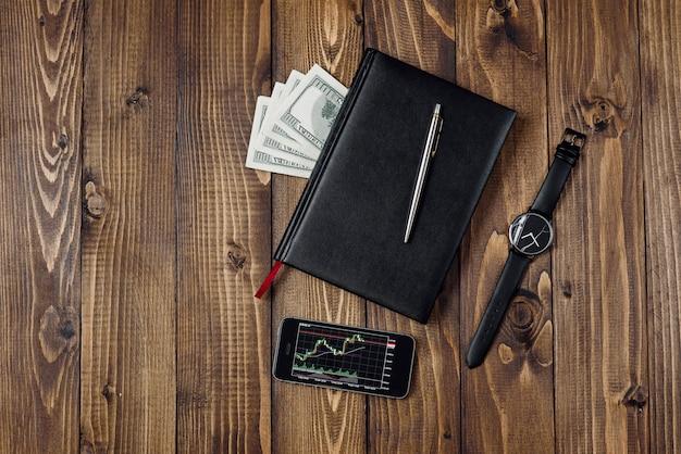 Vista superior del teléfono inteligente con gráfico financiero en pantalla, reloj, bolígrafo, cuaderno y dinero
