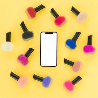 Vista superior del teléfono inteligente de pantalla en blanco con barniz de uñas colorido sobre fondo amarillo