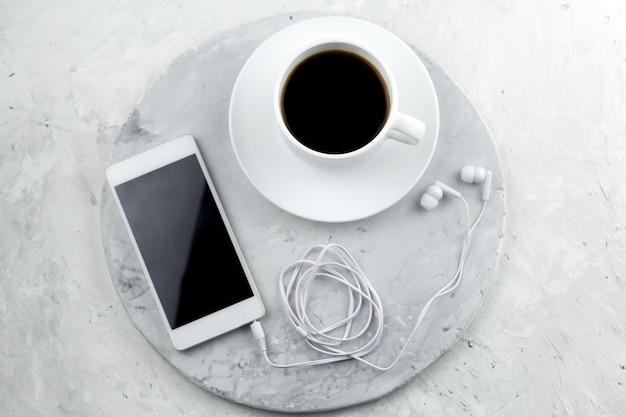 Vista superior del teléfono inteligente con pantalla vacía y taza de café en una mesa de mármol en la cafetería
